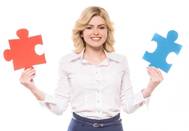 Vrouw in pak probeert stukjes van puzzel en glimlachen te verbinden