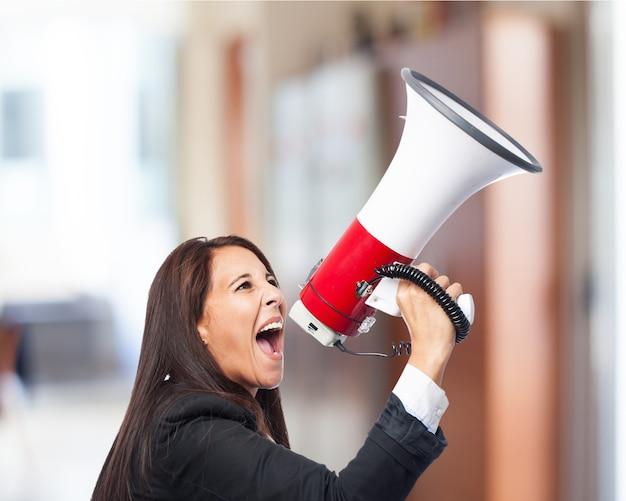 Vrouw in pak schreeuwen door een megafoon