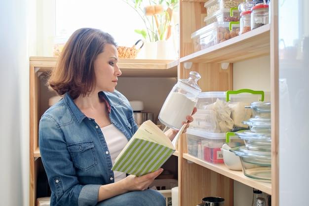 Vrouw in pantry met boodschappen, houten plank voor voedselopslag in de keuken