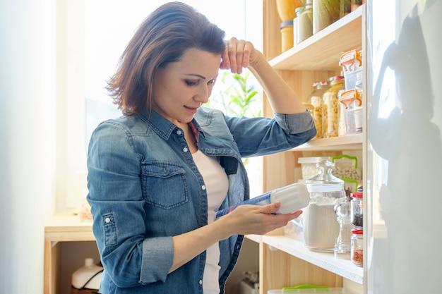 Vrouw in pantry met boodschappen, houten rek voor het bewaren van voedsel in de keuken
