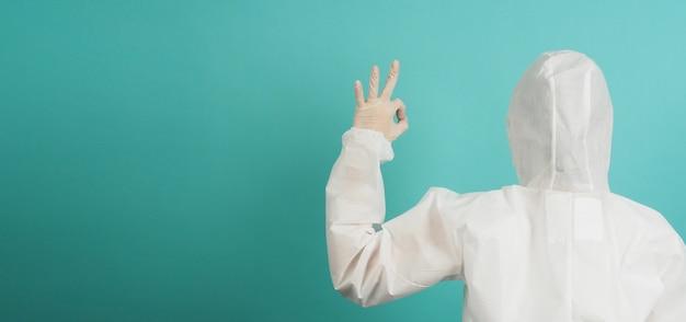 Vrouw in pbm-pak doet ok handteken op groene of tiffany blue achtergrond.