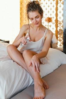 Vrouw in pijama die thuis lotion op lichaam toepast