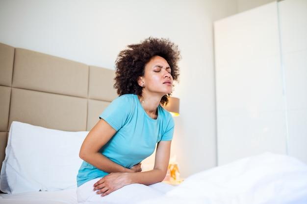 Vrouw in pijnlijke uitdrukking die handen houden tegen buik die aan menstruatiepijn lijden, droevig liggend op huisbed