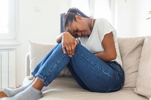 Vrouw in pijnlijke uitdrukking hand in hand tegen buik die last heeft van menstruatiepijn, verdrietig op thuisbed, buikkramp in vrouwelijk gezondheidsconcept