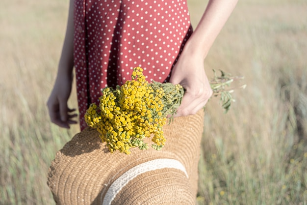 Vrouw in polka-dot jurk met boer hoed en boeket bloemen in haar hand, retro stijl vervaagde kleuren