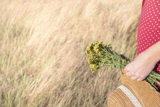 Vrouw in polka-dot jurk met boer hoed en boeket bloemen in haar hand