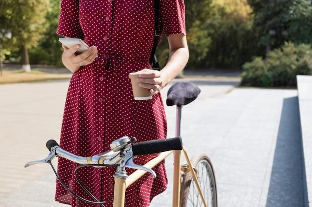 Vrouw in polka dot jurk met fiets woon-werkverkeer, mail checken online en koffie drinken. vrouwelijke persoon met behulp van smartphone en kopje warme drank te houden op weg naar haar werk