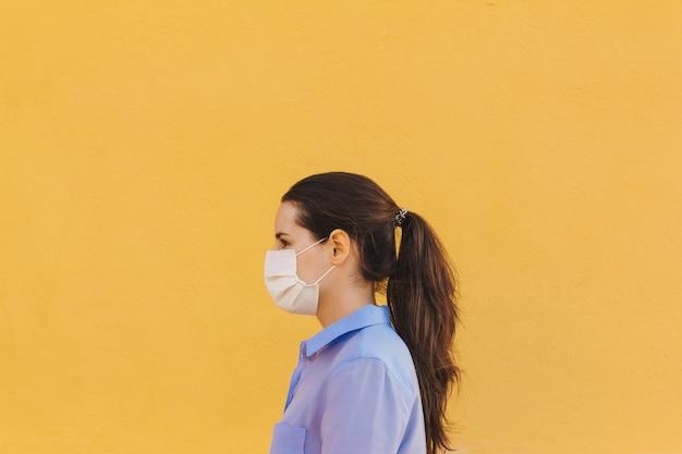 Vrouw in profiel met een gezichtsmasker en blauw shirt op een gele achtergrond
