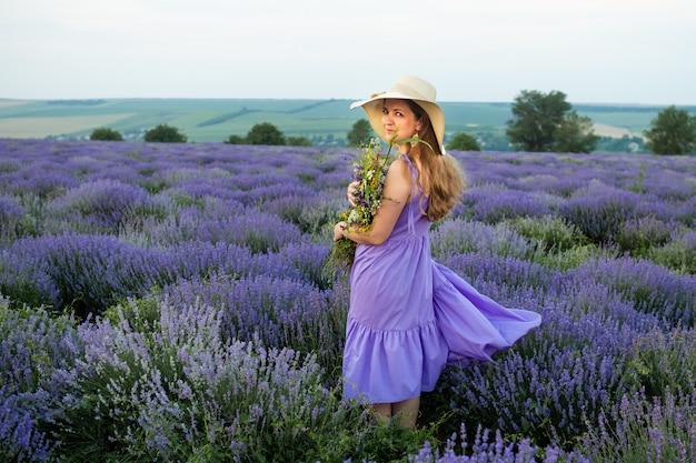 Vrouw in purpere kleding en hoed op lavendelgebied
