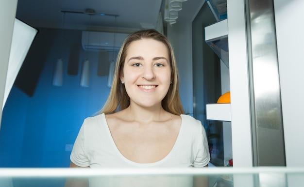 Vrouw in pyjama die 's avonds laat in de koelkast thuis kijkt