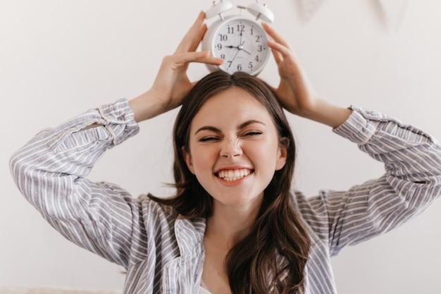 Vrouw in pyjama maakt mooi gezicht en houdt wekker op haar hoofd