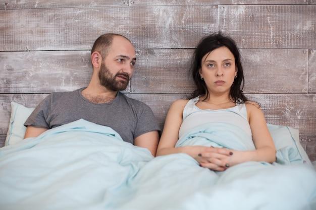 Vrouw in pyjama met emotioneel probleem die haar echtgenoot negeert.