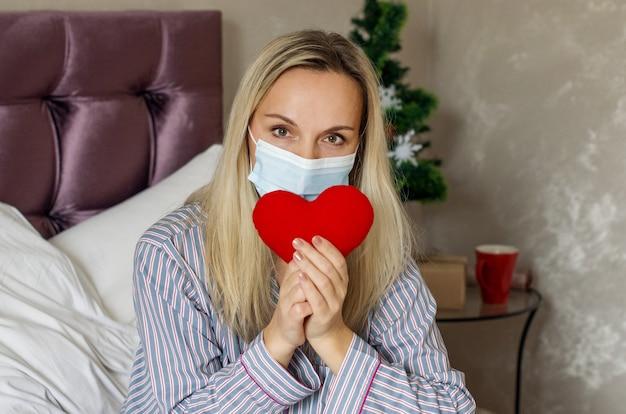 Vrouw in pyjama met medisch masker houdt een hart vast om kerstmis op bed te vieren