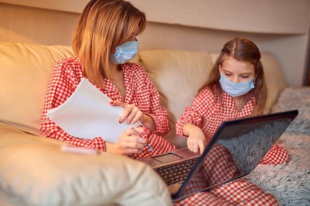 Vrouw in pyjama met notitieboekje en papieren werken vanuit huis met beschermend masker terwijl haar kind, dochter computerconsolespellen spelen