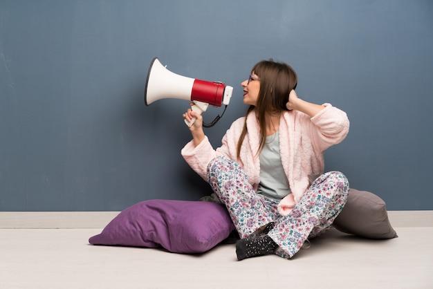 Vrouw in pyjama op de vloer die door een megafoon schreeuwt