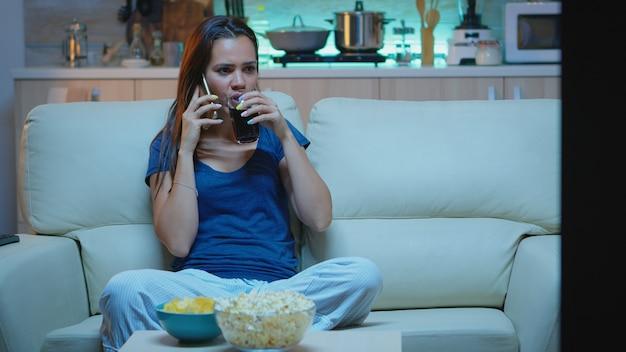 Vrouw in pyjama praten aan de telefoon tv kijken en snacks eten. gelukkige, ontspannen, eenzame dame in pyjama's genietend van de avond zittend op een comfortabele bank voor televisie sprekend op smartphone
