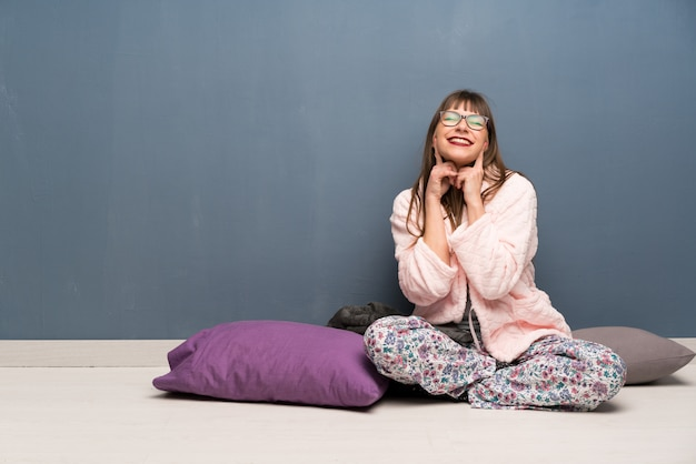 Vrouw in pyjama's op de vloer lachend met een gelukkige en aangename uitdrukking