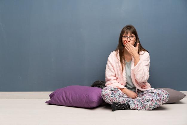 Vrouw in pyjama's op de vloerbedekking mond met handen voor ongepast zeggen