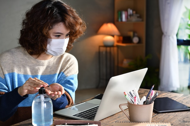 Vrouw in quarantaine en sociaal afstandelijk dragend chirurgisch masker en handen reinigend met alcoholgel ontsmettingsmiddel tijdens het werken vanuit huis tijdens covid-19 coronavirus pandemie