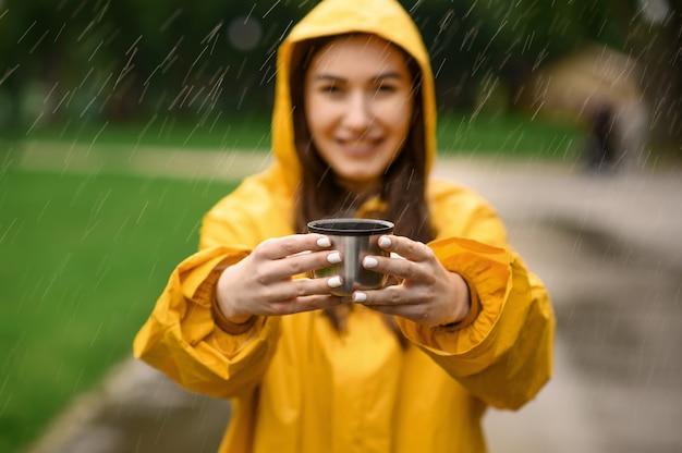 Vrouw in regenjas houdt kopje hete thee, zomerpark in regenachtige dag, uitzicht door de druppels. alleen vrouwelijke persoon in regenkaap op wandelpad, nat weer in steegje
