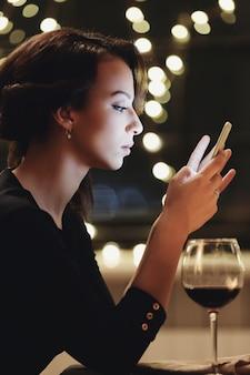 Vrouw in restaurant met behulp van de smartphone