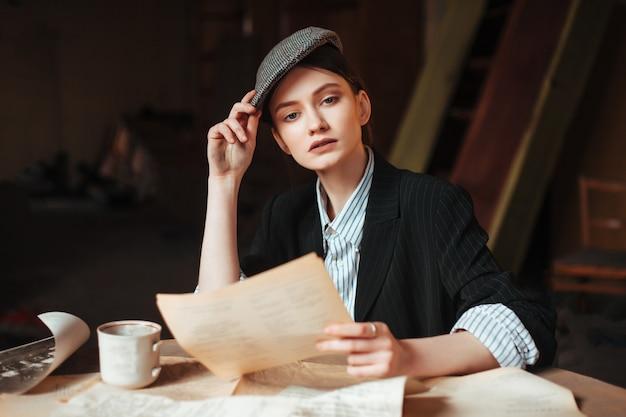 Vrouw in retro kleding voor mannen leest een brief