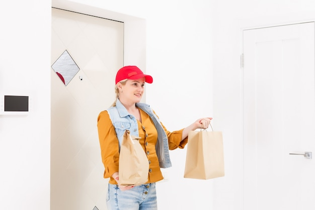 Vrouw in rode dop die de huisachtergrond van de snel voedselbestelling geeft. vrouwelijke koerier met papieren pakje met voedsel. levering van producten van winkel of restaurant aan huis. ruimte kopiëren