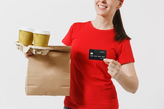 Vrouw in rode dop, t-shirt geven fastfood bestelling geïsoleerd op een witte achtergrond. vrouwelijke koerier met creditcard, papieren pakje met eten, koffie. levering van producten van winkel of restaurant aan huis.