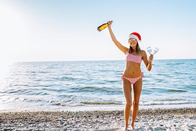 Vrouw in rode en witte bikini en kerstmuts met champagne op een strand.