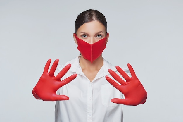 Vrouw in rode handschoenen en gezichtsmasker