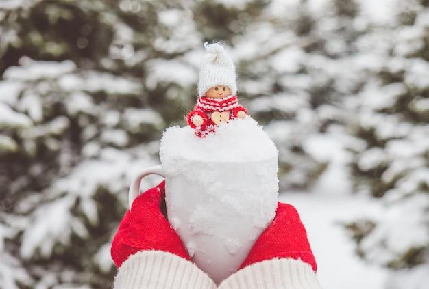 Vrouw in rode handschoenen houdt de mok met sneeuw en schattig kerstspeelgoed erin.