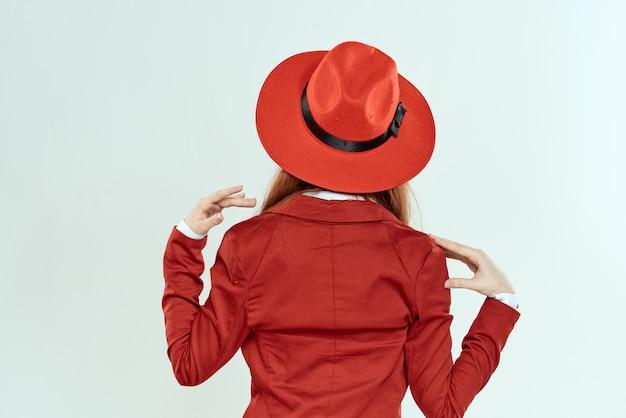 Vrouw in rode hoed en jasje achteraanzicht elegante stijl lichte achtergrond