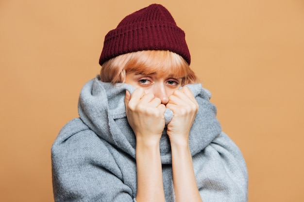 Vrouw in rode hoed en warme sjaal met rode pijnlijke ogen die de eerste symptomen van griep voelen, camera kijken