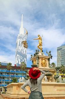 Vrouw in rode hoed onder de indruk van de prachtige neptunus-fontein op theaterplein in batumi