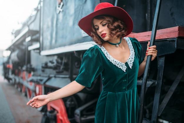 Vrouw in rode hoed op vintage stoomlocomotief. oude trein. spoorwegmotor, treinreis