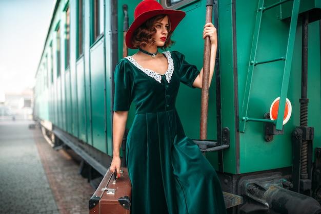 Vrouw in rode hoed tegen oude treinwagon. retro trein. spoorwegreis