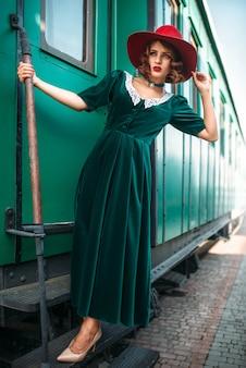 Vrouw in rode hoed tegen oude treinwagon Premium Foto