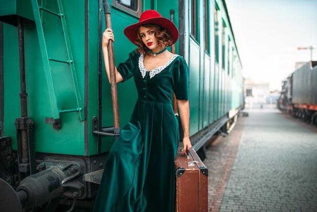 Vrouw in rode hoed tegen oude treinwagon