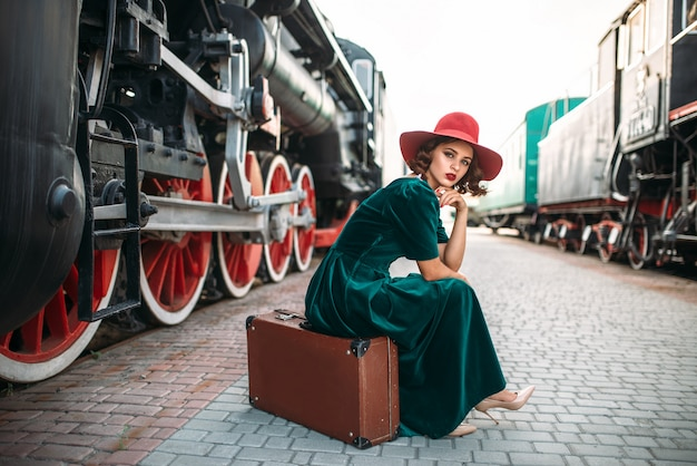 Vrouw in rode hoed tegen vintage stoomtrein