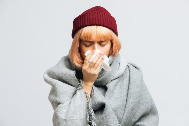 Vrouw in rode hoed, warme sjaal met papieren servet niest, ervaart allergiesymptomen, verkouden