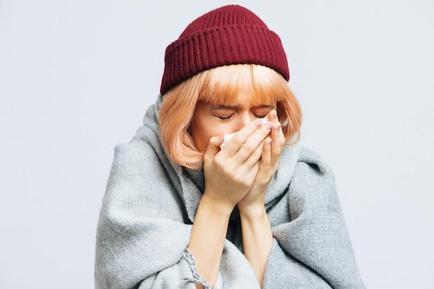 Vrouw in rode hoed, warme sjaal met papieren servet niest, ervaart allergiesymptomen, ving koude, gesloten ogen