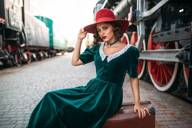 Vrouw in rode hoed zittend op koffer tegen vintage stoomtrein. oude locomotief. spoorwegmotor, oud spoorwegvoertuig