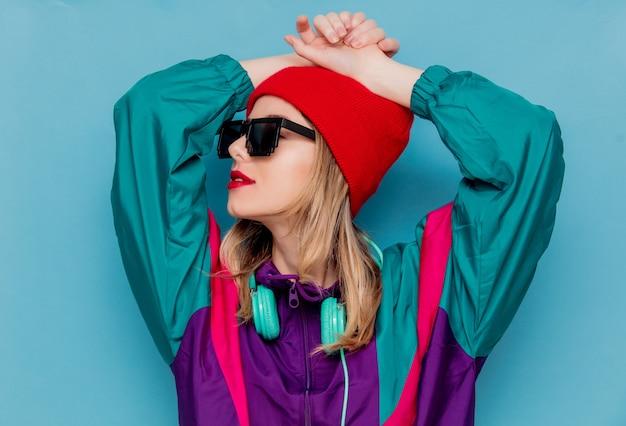 Vrouw in rode hoed, zonnebril en pak van de jaren 90 met een koptelefoon
