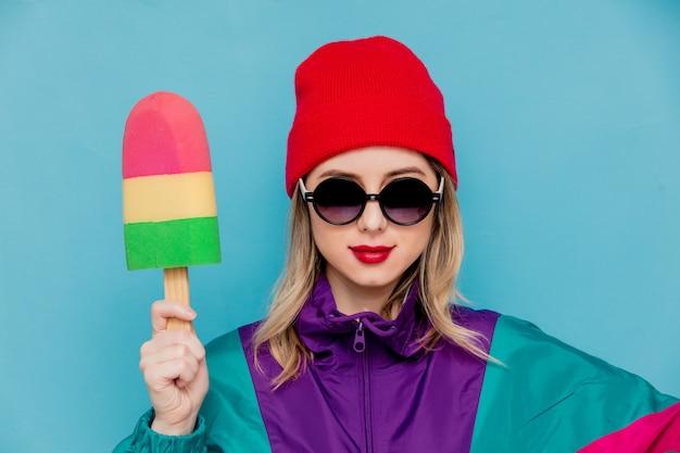 Vrouw in rode hoed, zonnebril en pak van de jaren 90 met speelgoed-ijs