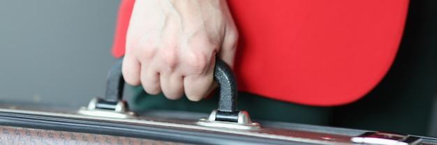 Vrouw in rode jas bedrijf koffer close-up verplaatsen in het buitenland concept