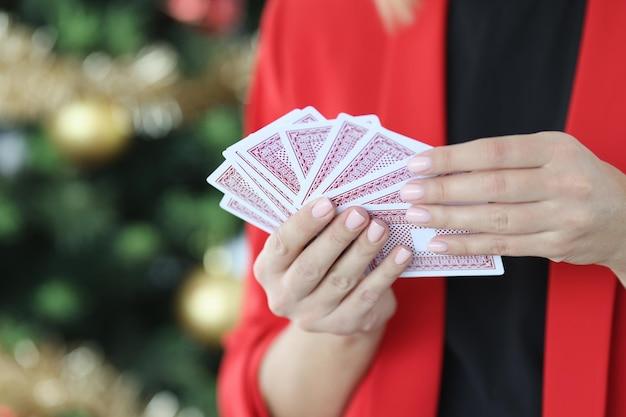 Vrouw in rode jas houdt speelkaarten vast tegen de achtergrond van nieuwjaarsboom kerstmis en