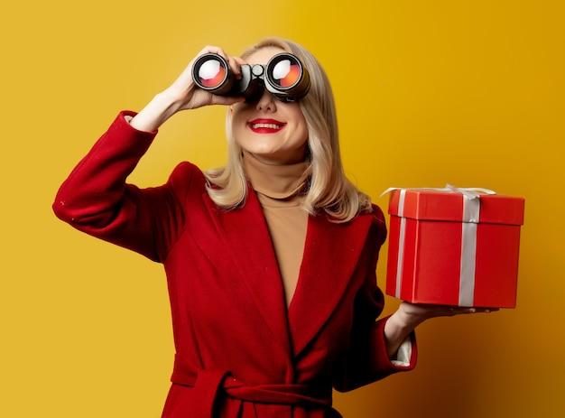 Vrouw in rode jas met verrekijker en geschenkdoos op gele muur