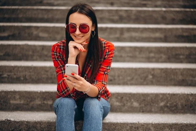 Vrouw in rode jas zittend op de trap met behulp van de telefoon