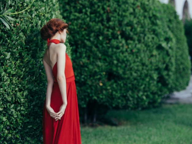 Vrouw in rode jurk elegante stijl tuin natuur poseren