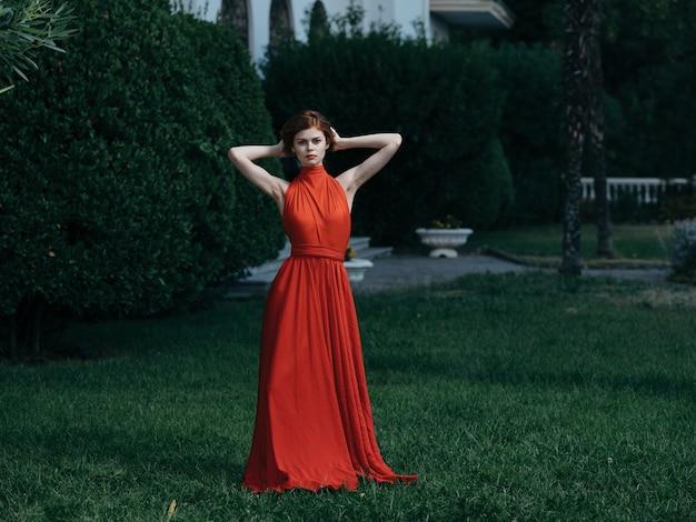 Vrouw in rode jurk groen gras park luxe charme model